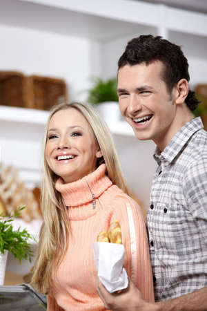 Attractive couple with rolls in shop Stock Photo - 7743285