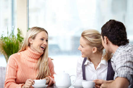 foreground: Smiling people drink coffee in the foreground  Stock Photo