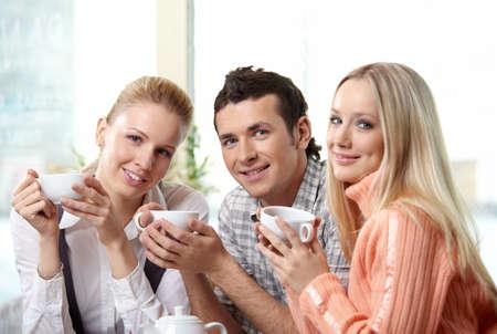 mujer tomando cafe: Nice j�venes beben caf� sobre un fondo hacia adelante