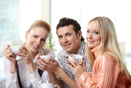 Nice young people drink coffee on a forward background photo