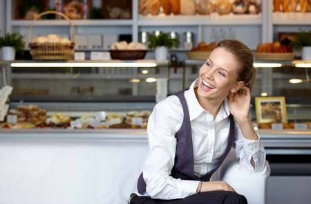 nice girl: The young nice girl at a show-window with cakes Stock Photo