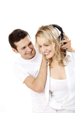 woman listening to music: The young man puts on ear-phones to the lovely girl