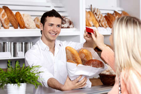 The seller sells to the girl bread in a bakery photo