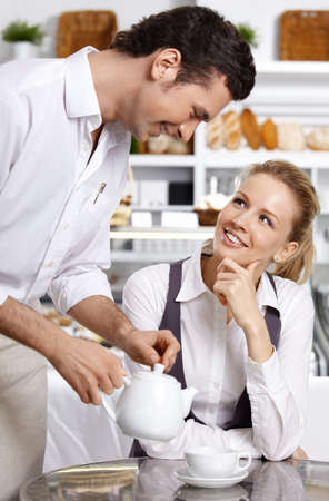 The waiter pours tea to the attractive girl Stock Photo - 7841397