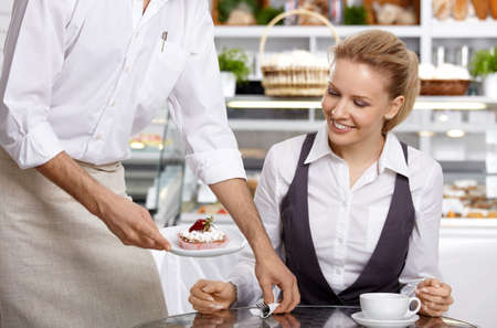 brings: Il cameriere porta al visitatore il dessert ordinato  Archivio Fotografico