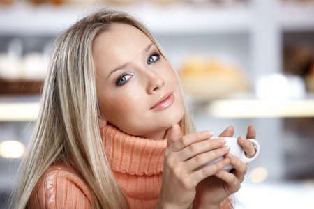 woman drinking coffee: The young beautiful girl with a cup Stock Photo