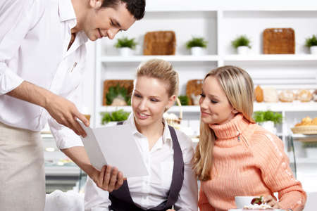 waiter: The young waiter shows the menu to two girls