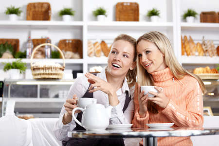 women laughing: The young girl shows on something to the girlfriend in cafe