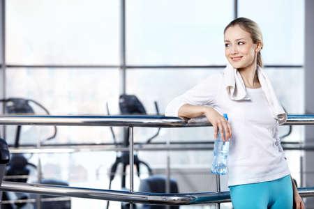 sports form: La ragazza in forma sportiva con una bottiglia nel palazzetto dello sport