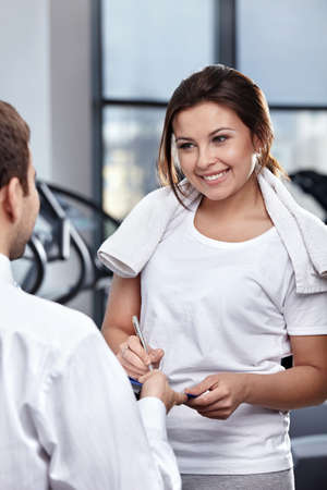The nice young girl appends the signature in gym photo