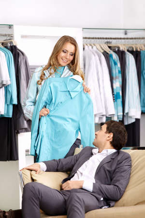 personal shopper: The girl shows to the man a shirt in shop