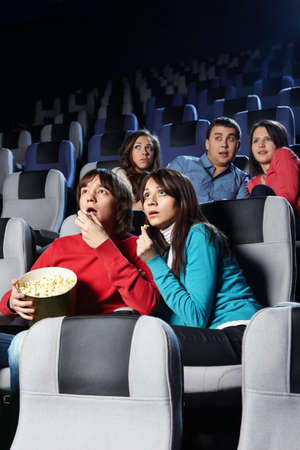 Group of young people look a film at a cinema photo
