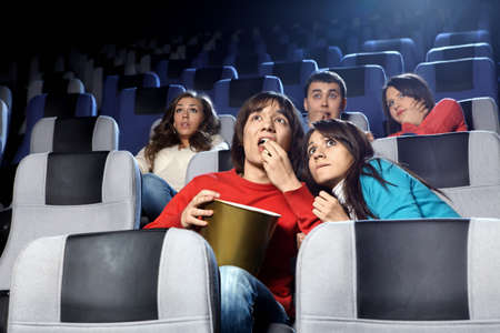 The scared young people at cinema viewing photo