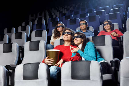 Smiling young people look cinema in 3d photo