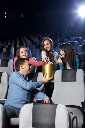 The young man at cinema gives girls pop-corn Stock Photo - 7841940