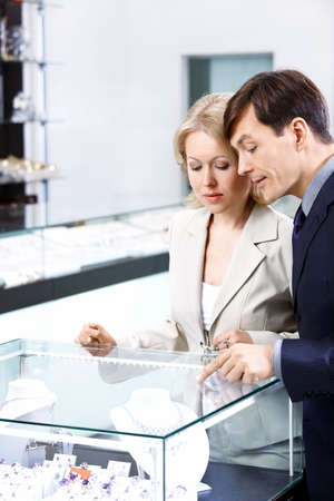 specifies: The man specifies to the woman in a jewel in shop  Stock Photo