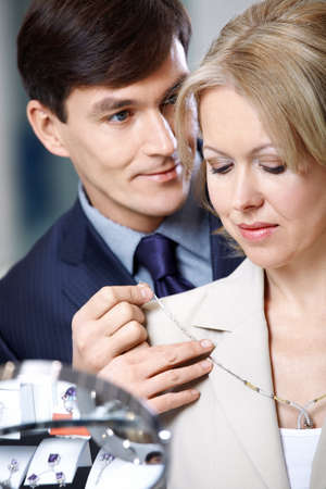 The man puts on to the woman a jeweller necklace  photo