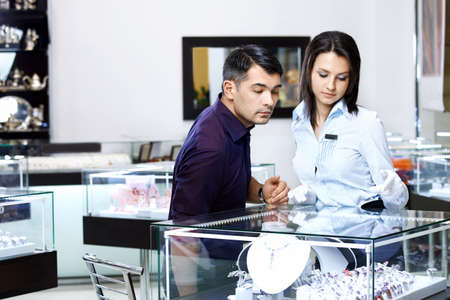The girl-seller shows to the visitor assortment in jeweller shop  photo