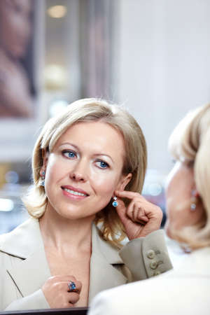 one senior adult woman: The woman of middle age tries on earrings at a mirror