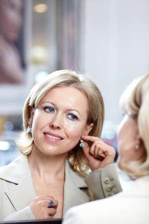 mirar espejo: Trata de la mujer de mediana edad en aretes en un espejo  Foto de archivo