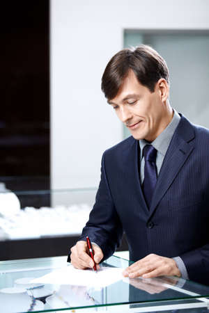 The businessman of average years signs papers photo