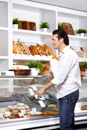 The young man points a finger at a product which wishes to buy  Stock Photo - 7841610