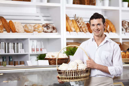 The young seller holds a basket with cakes in shop  photo
