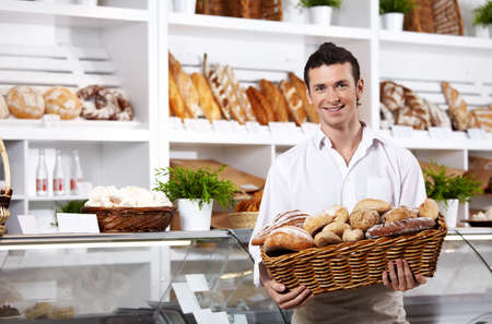 bakery  bread: The seller in shop holds a basket with rolls