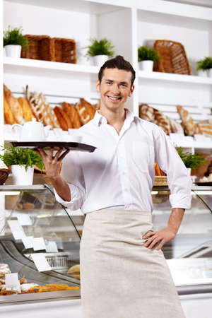 The young waiter holds a tray in the foreground Stock Photo - 7841609