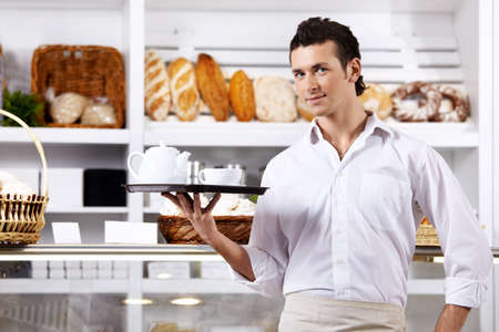 The young man with a tray against a show-window Stock Photo - 7841365