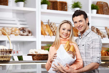 Young attractive couple with bread in shop  photo