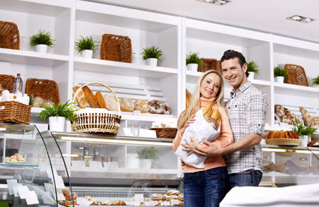 Young attractive couple with a package of rolls in shop photo