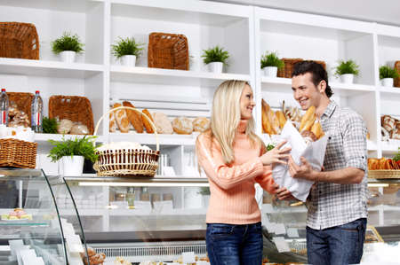 bagged: Young attractive couple with bread in shop  Stock Photo