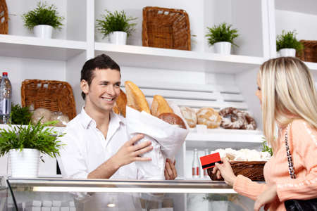 The attractive girl buys bread in shop photo