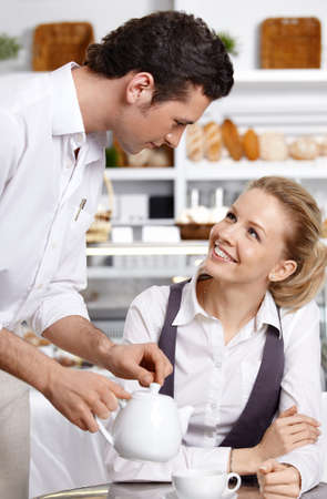 The young waiter with the client in cafe Stock Photo - 7841380