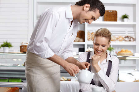 The waiter pours tea to the attractive girl in cafe photo