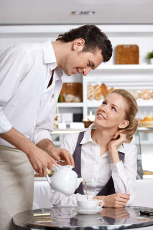 The young waiter pours tea to the client in cafe photo