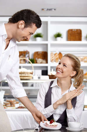 The waiter has brought to the girl a dessert in cafe Stock Photo - 7841375