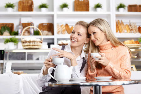 Two beautiful girls discuss something in cafe  photo