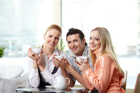 Young attractive people in cafe with cups photo
