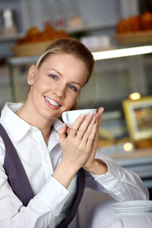 The beautiful girl with a cup in the foreground in cafe photo
