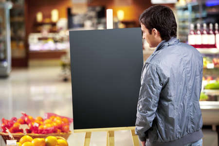 The young man looks at an empty board in shop Stock Photo - 7841486