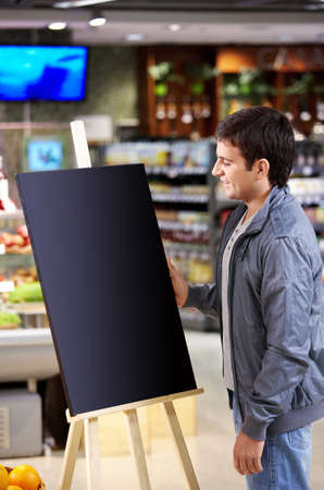 The young man faces to an empty board in shop Stock Photo - 7841488