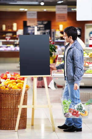 The man looking at an empty board with a basket with meal in shop Stock Photo - 7841756