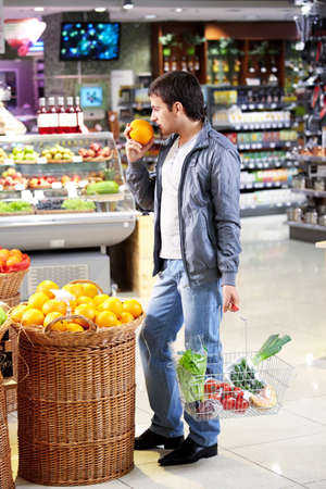The man chooses a grapefruit in shop Stock Photo - 7841994