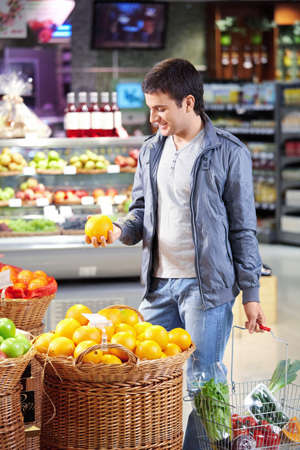 The man with a basket of products chooses a grapefruit in shop Stock Photo - 7841985