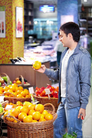 The young man holds an orange in shop Stock Photo - 7842020