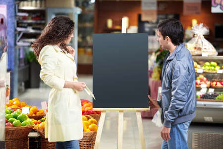 The man and the woman look at an empty board in shop Stock Photo - 7841565
