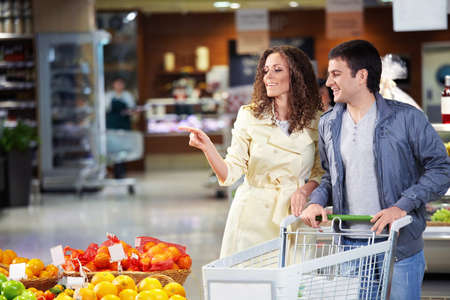 The young couple with the cart goes on shop photo