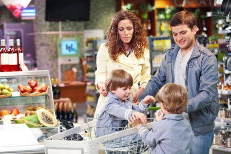 ni�os de compras: Familia feliz con los ni�os en la tienda de abarrotes  Foto de archivo
